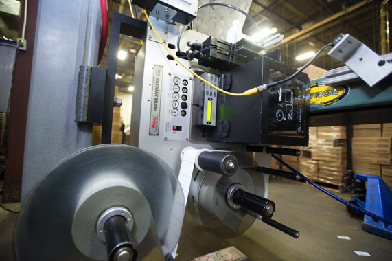 A roll of pressure-sensitive labels processed by a high-speed printer-applicator from Weber for precise application of individual labels onto the corrugated shipping boxes.