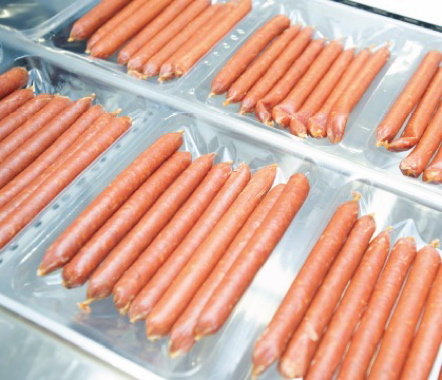 Pepperoni sticks are hand-placed onto the bottom film layer on the VC999 RS420c thermoforming machine, before a top layer of film is added to seal in the flavor.