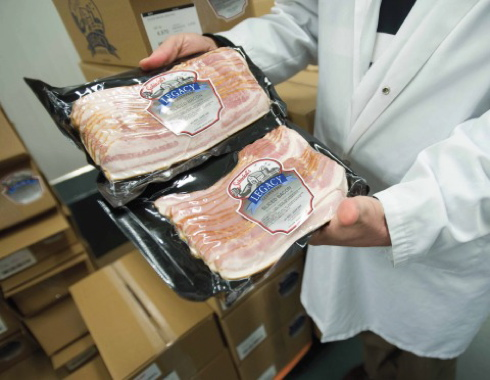 A plant employee holding one-pound packs of Schinkel's Legacy bacon in the high-quality packages created by the company's newly-purchased VC999 model RS420c thermoform machine.
