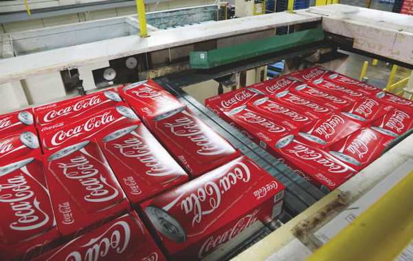 Filled cases of Coca-Cola cans are arranged into their assigned layer patterns for stacking on one of the Weston facility's two fully-automatic T-Tek palletizing stations positioned directly below on the plant floor.