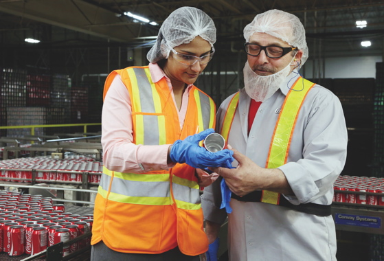 Kavitha Naidu and plant lead-hand Frank Stirpe conduct a random quality check on an empty can pulled off the fast-moving Line One to inspect for any signs of denting or other points of impact that can result in a product defect.