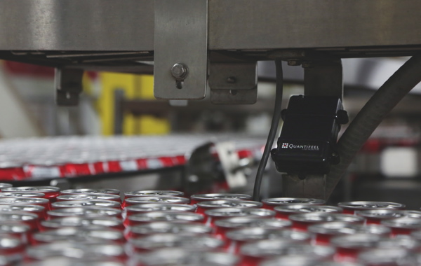 One of many Quantifeel tags installed above the fast-moving rows of filled cans of Coca-Cola cans picks up real-time line status updates from the red drone can also traveling along the conveyor belt to locate excessive pressure points.