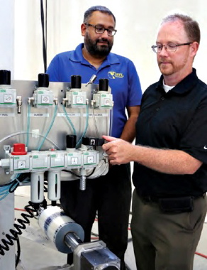 APPE's Al Aman (left) and ASCO's John Lamb examining the Vertobagger 2.0's Numatics air prep devices air regulators (smaller ones on top), and the larger FRL - filter regulator with air purge that cumulatively cleans and filters impurities from the air entering the machine, as well as removing all air when the Emergency Stop button is pressed.