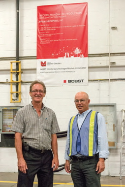 Mitchel-Lincoln Packaging vice-president of operations Pierre Aubry (left) and Jimmy Garfinkle stand underneath a large banner from Bobst acknowledging the world-record 162,136 boxes processed on the 8.20 EXPERTLINE over an eight-hour shift.